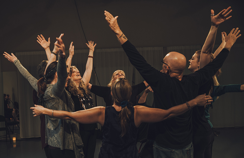 circle of 8 dancers, 7 women and 1 man, reaching their arms into the air, looking up and smiling